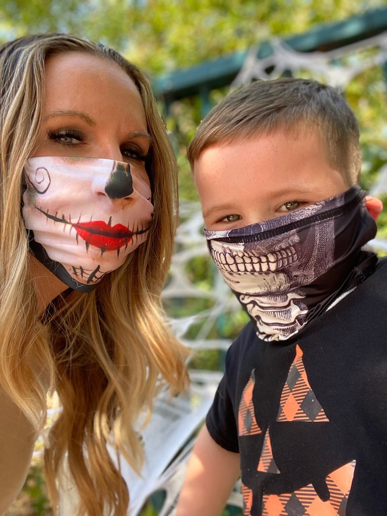 Woman and boy taking a selfie wearing skeleton masks.  Guide to Six Flags over Texas Hallowfest
