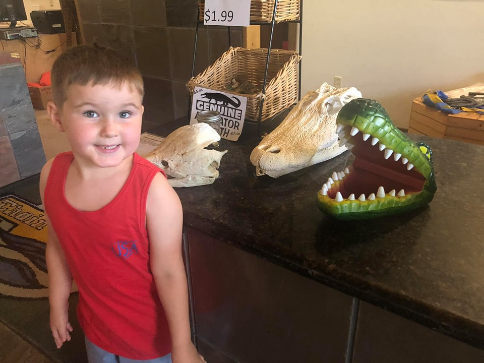 Little boy posing with display alligators at the lake.| The Retreat at Artesian Lakes in Texas