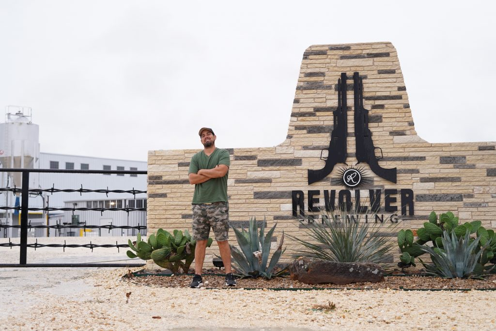 Man standing in front of Revolver Brewing Company sign.   A Guide to Granbury, Texas