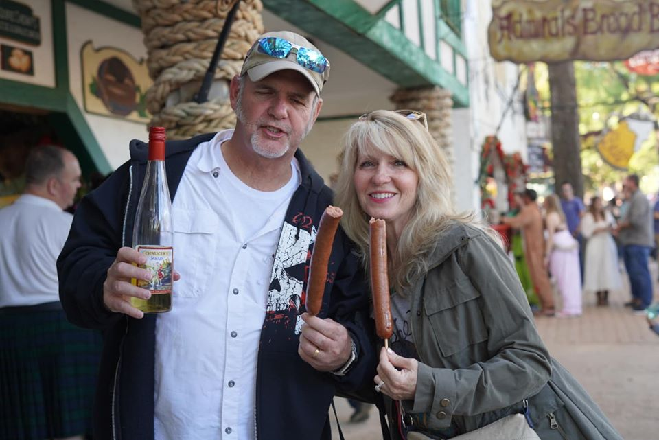 Couple posing with sausage on a stick outside. | Texas Renaissance Festival