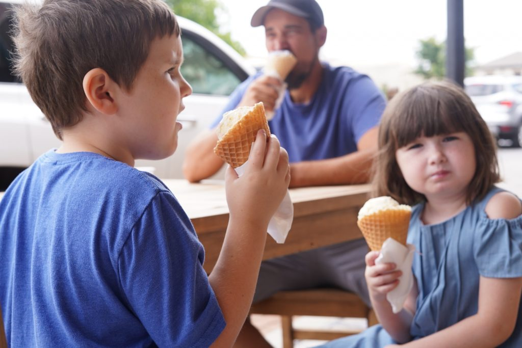 Man with kids eating ice cream at Silversaddle Saloon.   A Guide to Granbury, Texas