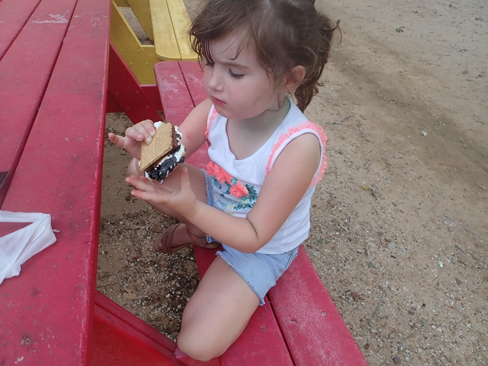 Little girl eating s'mores at Jellystone in Texas.   Jellystone Park in Waller, Texas