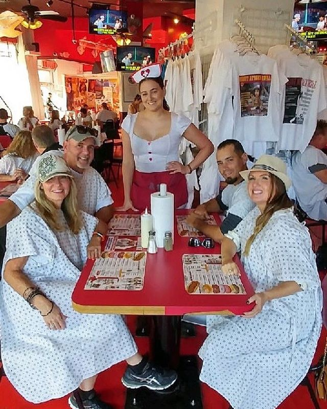Group of people dressed in hospital gowns posing at the table at Heart Attack Grill. | Las Vegas- A Guide to Vegas