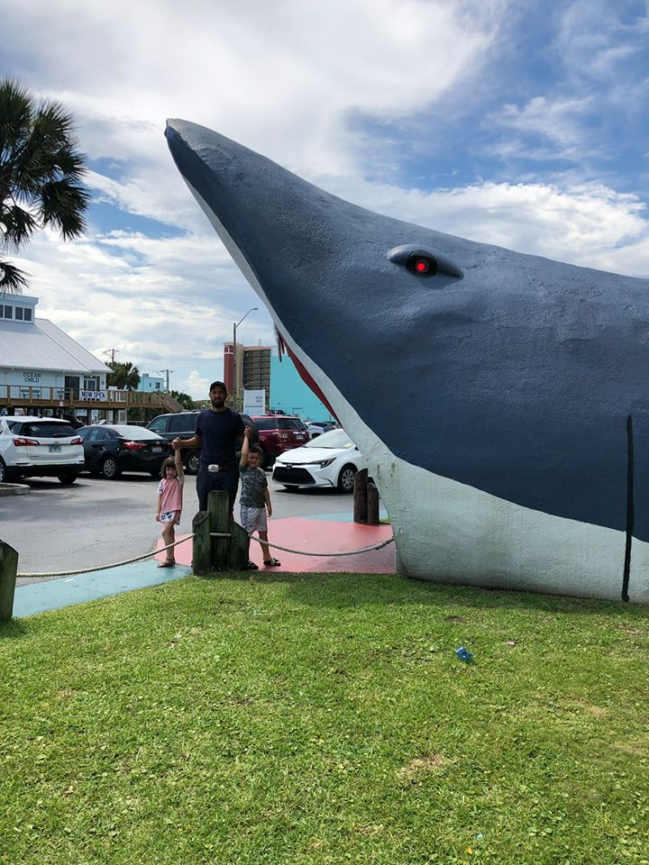 Man with his two kids posing with a large shark statue.   Guide to Gulf Shores & Orange Beach Alabama