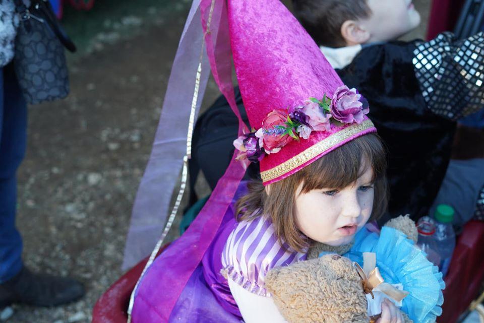 Little girl wearing crown souvenir on the sidewalk outside. | Texas Renaissance Festival
