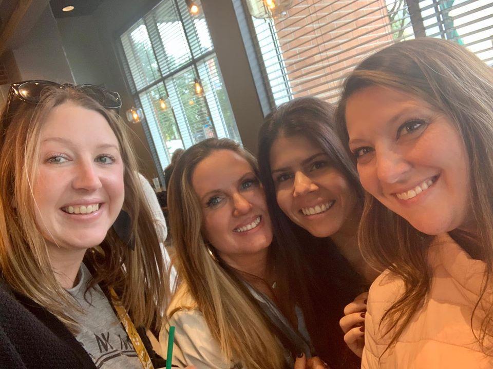 Women posing for a group picture inside Starbucks.  Girls Weekend Getaway- Woodlands, TX
