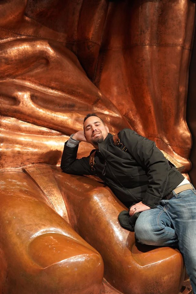 Man posing with statue in the Statue of Liberty Museum.   New York City