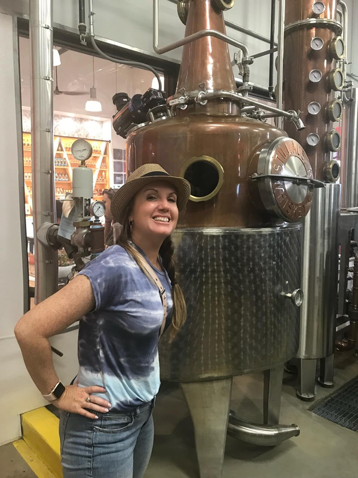 Woman posing with equipment inside Still Austin Whiskey Company in Austin.  Weekend Guide to Austin, Texas