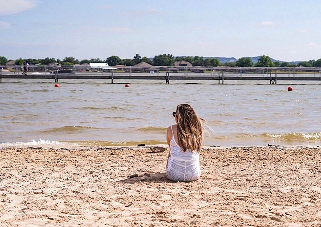 Woman sitting on the beach looking at the lake.   A Guide to Granbury, Texas