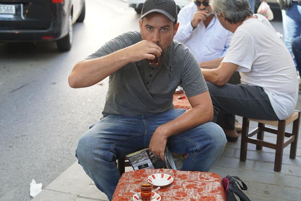 Man drinking hot tea at a restaurant table outside on the sidewalk. | Istanbul, Turkey