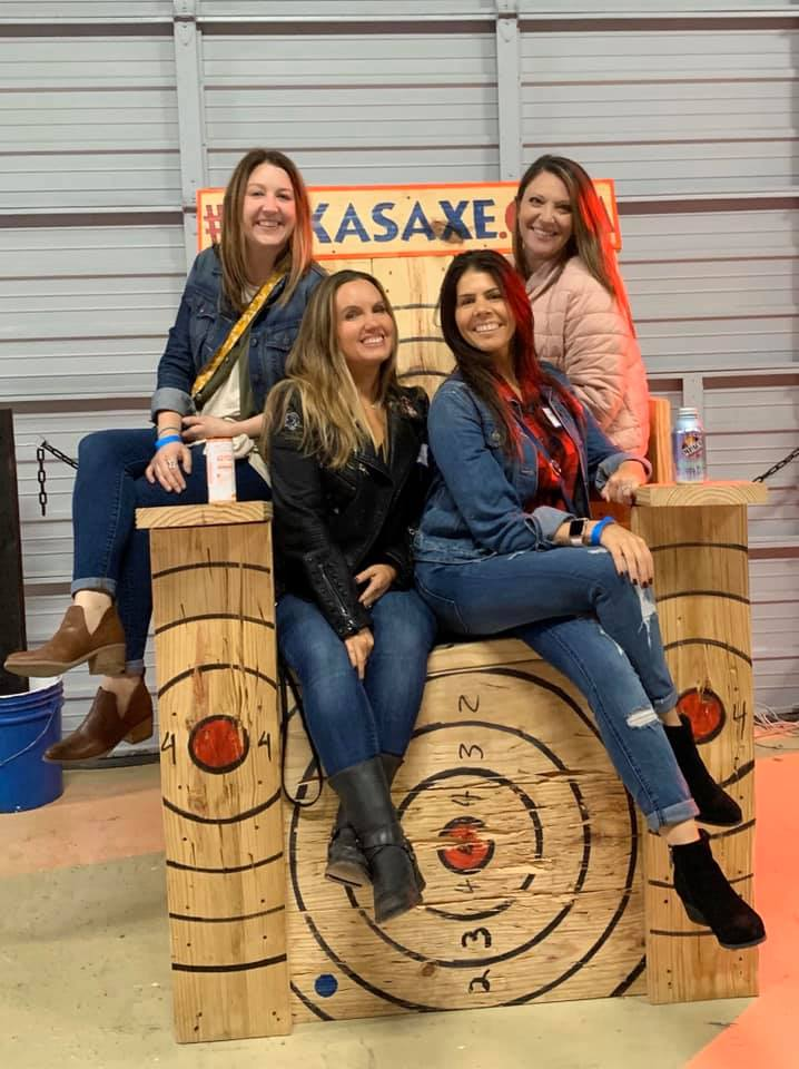 Women posing on the large wooden chair at Texas Axe Throwing   Girls Weekend Getaway- Woodlands, TX