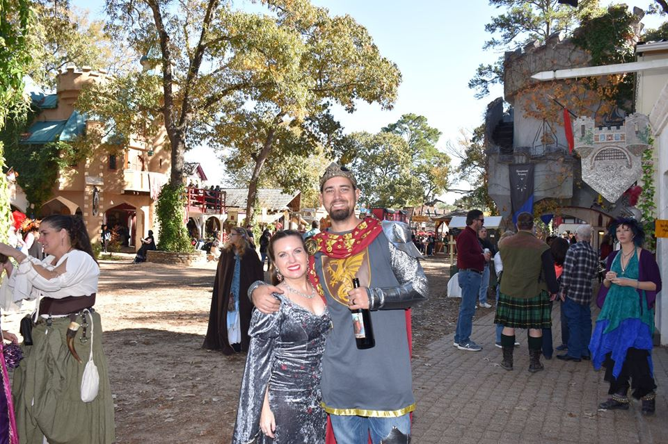Couple dressed in renaissance clothing with crowds behind them. | Texas Renaissance Festival