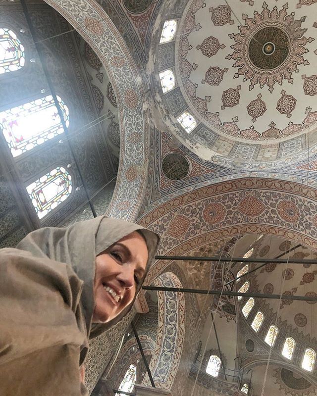 Woman posing in The Blue Mosque which is a famous historical mosque located in Istanbul. The name comes from the blue tile that surrounds the interior walls. | Istanbul, Turkey