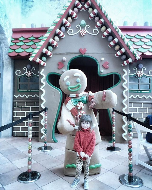Little girl posing in front of large gingerbread man at the Gaylord Texan in Texas. | Christmas at the Gaylord Texan Hotel