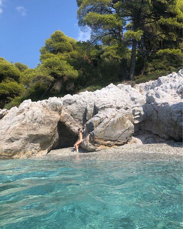 Woman sitting on the rocks on the shore of the Kastani Beach. | Skopelos Island, Greece- Mamma Mia Island