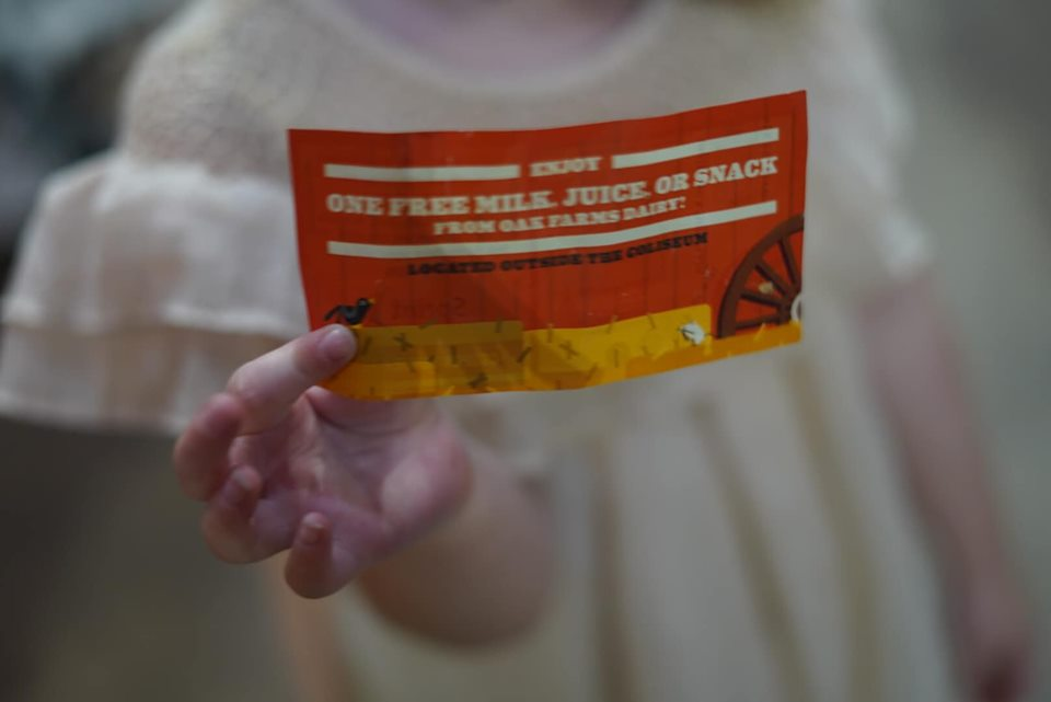 Little girl holding free coupon in the animal area at the fair. | State Fair of Texas-Dallas