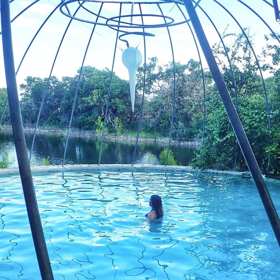 Woman swimming in the pool at Cypress Valley. | Cypress Valley Canopy Tour in Austin, Texas