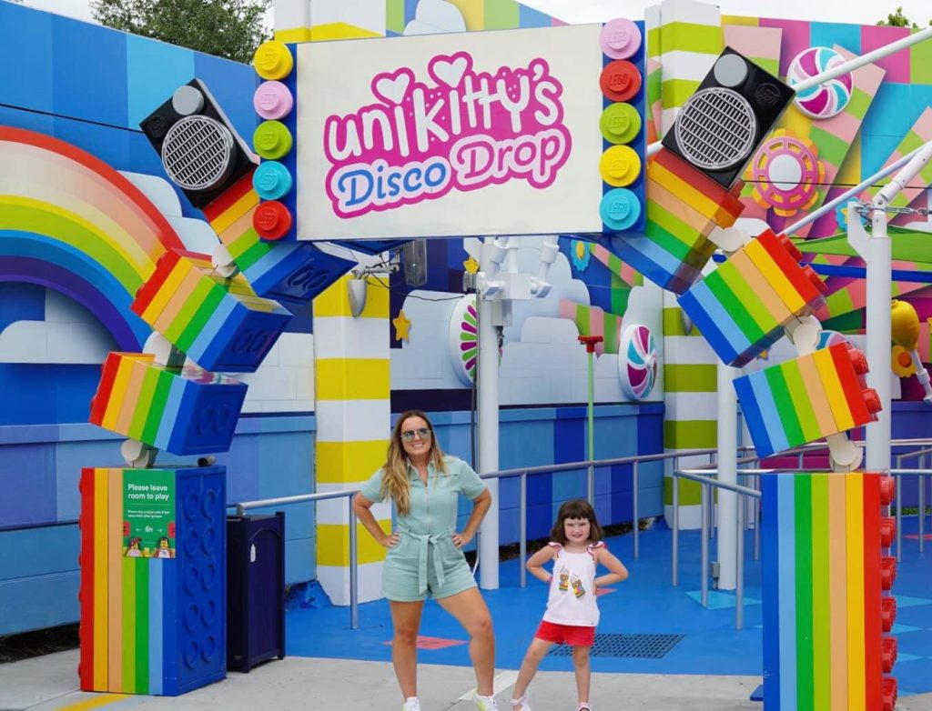 Mom and daughter posing in front of Unikitty's Disco Drop.  Guide to LEGOLAND Florida