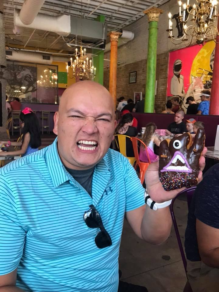 Man posing with a funny donut at Voodoo Donuts in Austin.  Weekend Guide to Austin, Texas