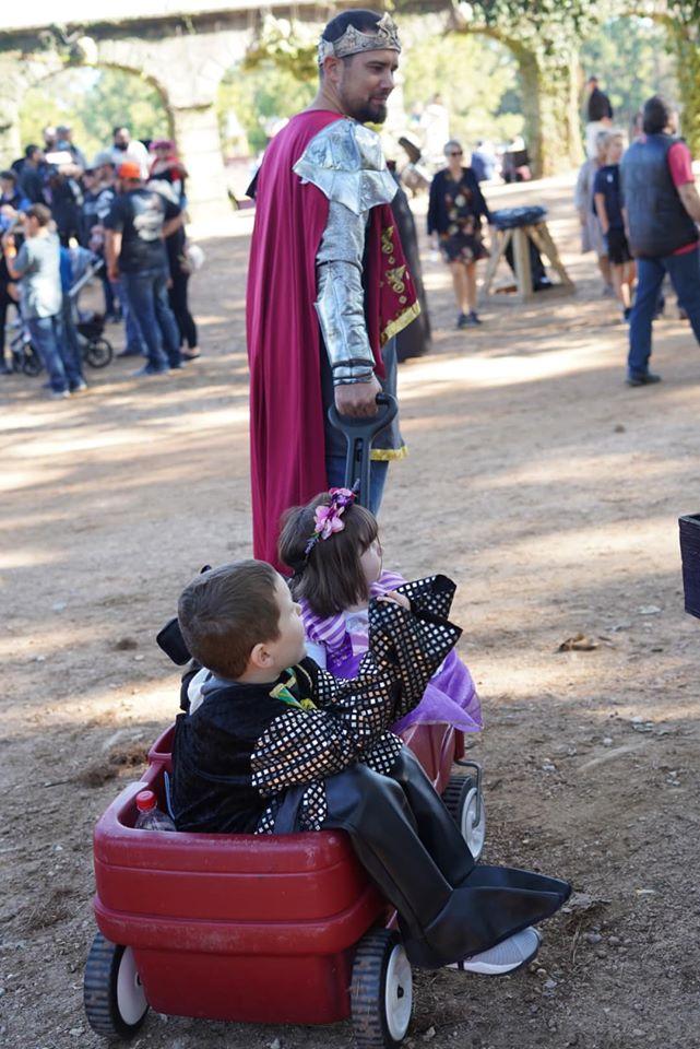 Man pulling wagon full of kids down the dirt road. | Texas Renaissance Festival