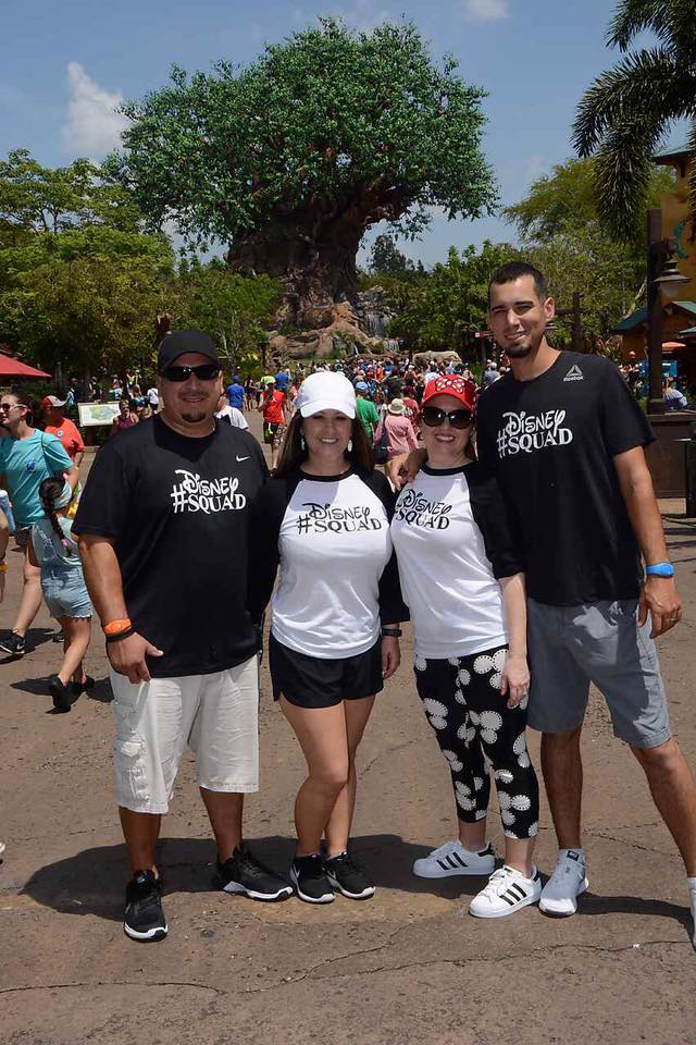 Two couples posing in Animal Kingdom wearing matching #DisneySquad shirts at Disney World.   Celebrating A Wedding Anniversary at Walt Disney World