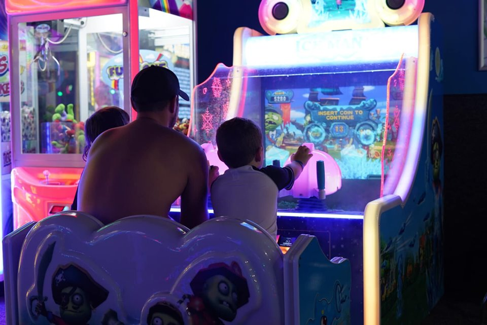 Man and two kids playing games at arcade at Epic.| Epic Waterpark in Dallas, Texas