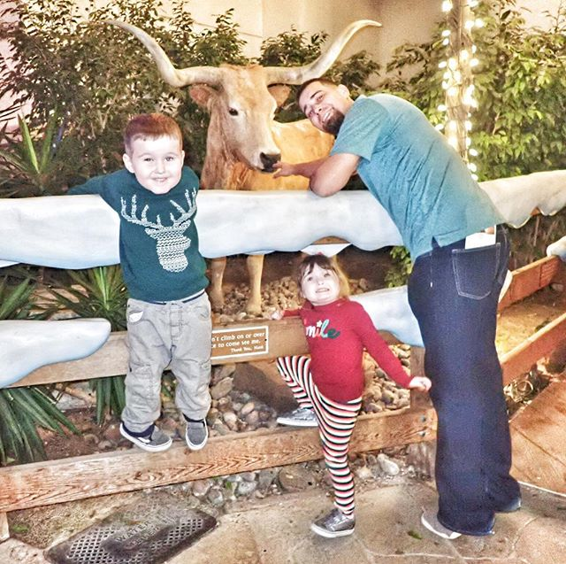 Dad with two kids posing with animal statues at the Gaylord Texan in Texas. | Christmas at the Gaylord Texan Hotel