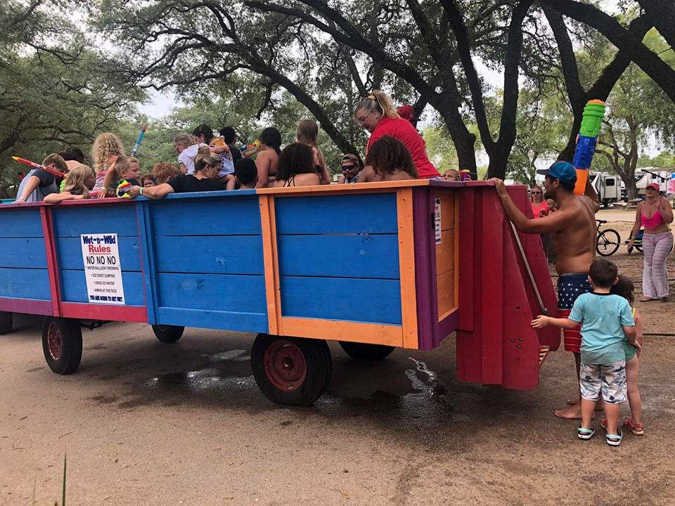 Kids riding Wet and Wild Wagon Ride at Jellystone in Texas.   Jellystone Park in Waller, Texas