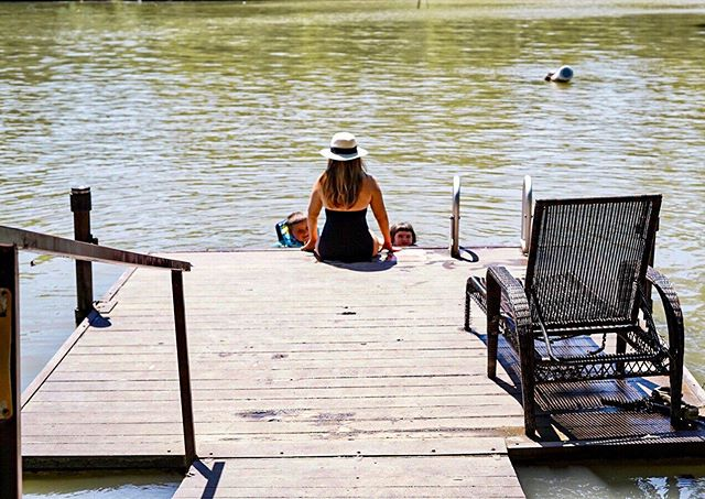 Woman sitting on the edge on the pier with kids in the water swimming at Son's Island.| Son's Island in Seguin, Texas