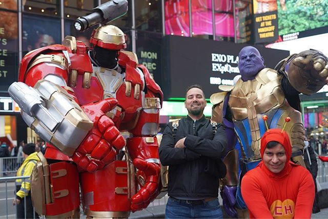 Man posing with superhero characters on the street.   New York City