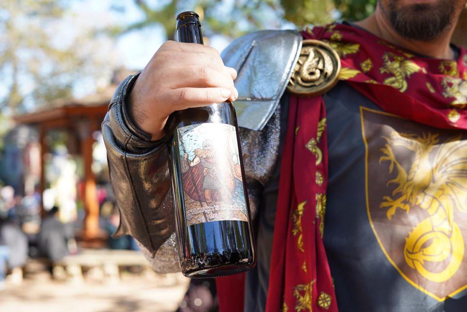 Man holding a bottle of wine outside.| Texas Renaissance Festival