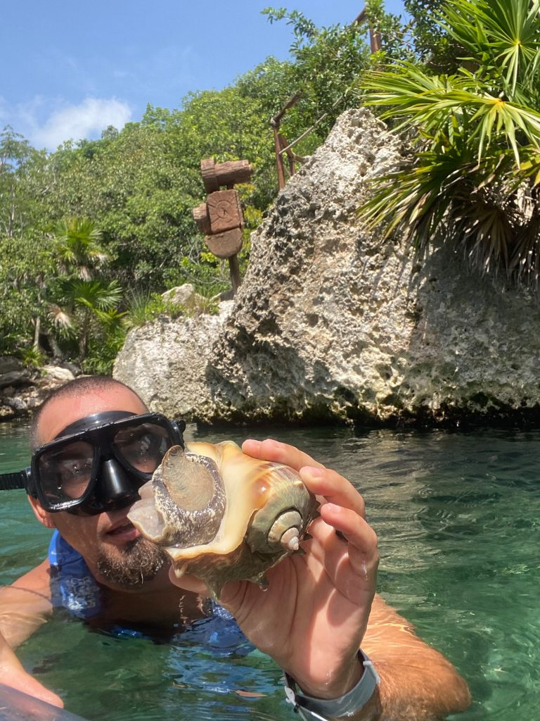 Man swimming posing with seashell he found. | All About XeI-Ha Park in Riviera Maya