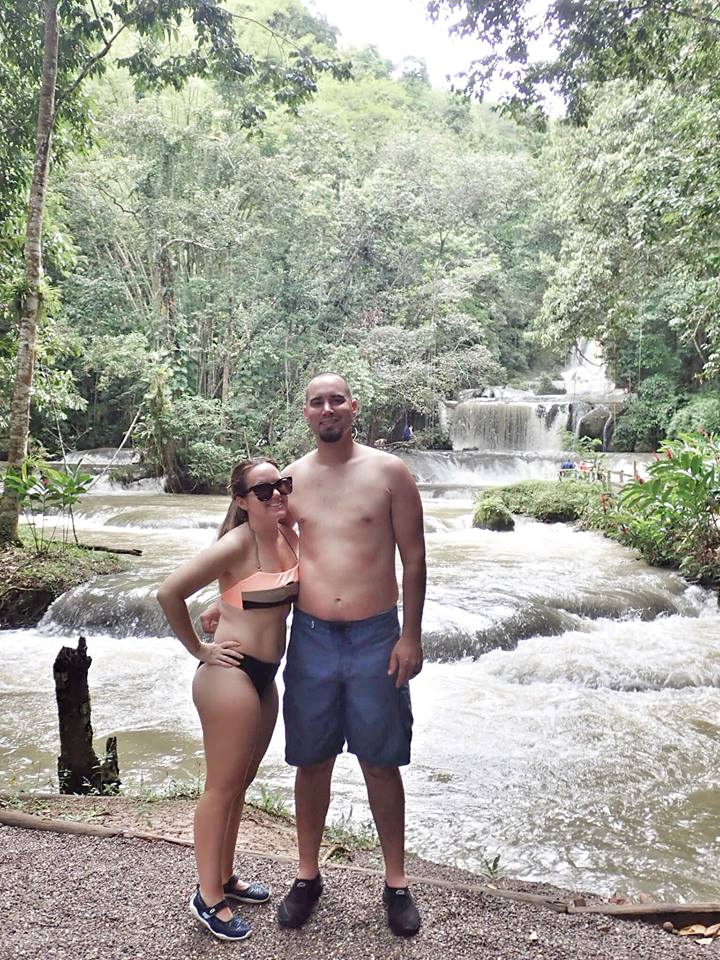 Couple posing in front of waterfall at YS Falls Excursion in Jamaica.   Jamaica Over-Water-Bungalows