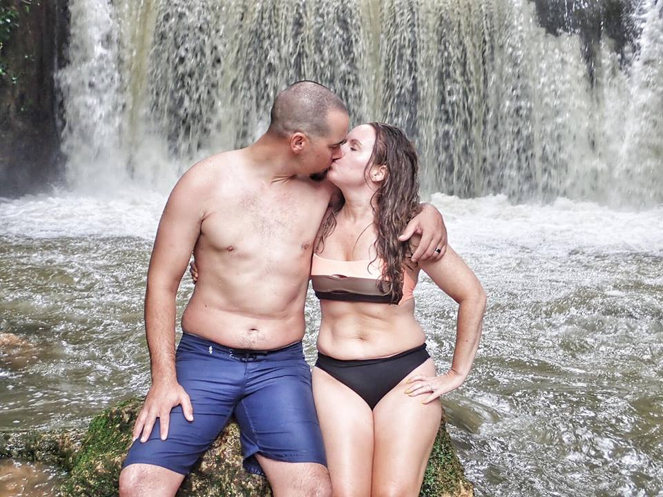 Couple kissing in front of waterfall at YS Falls Excursion in Jamaica.   Jamaica Over-Water-Bungalows