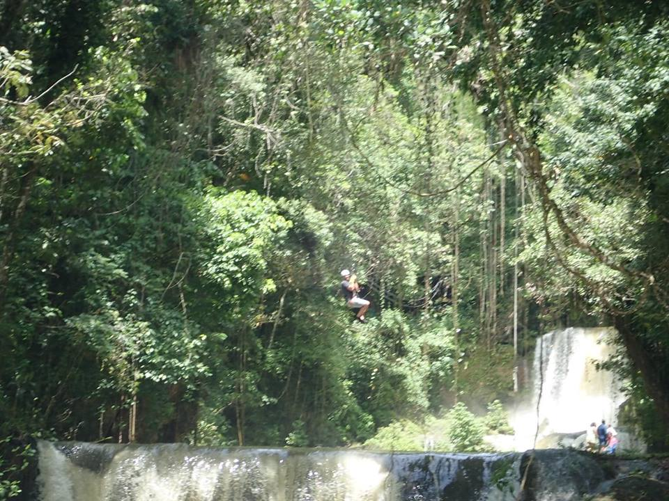 Man ziplining in the jungle at YS Falls Excursion in Jamaica.   Jamaica Over-Water-Bungalows