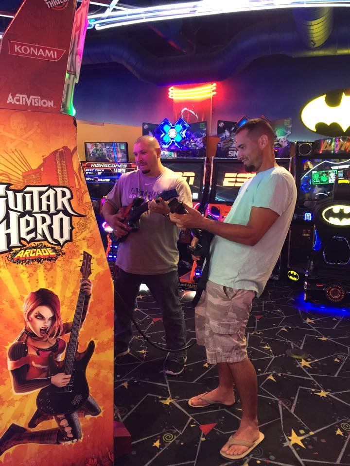 Two men playing video arcade games at Kemah Boardwalk. | Kemah Boardwalk in Texas