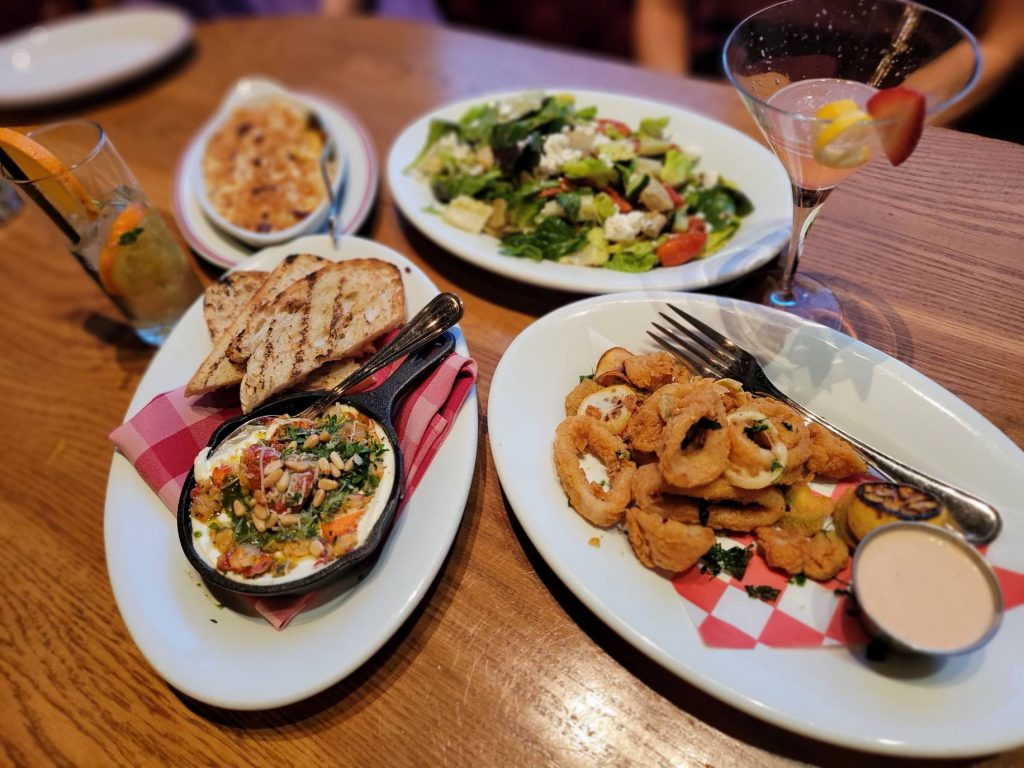 Plates of appetizer food with two drinks on a table.   Where to eat in Las Vegas