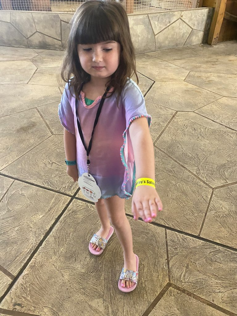 Little girl showing off her wrist band for access to the waterpark.  Great Wolf Lodge in Grapevine, Texas