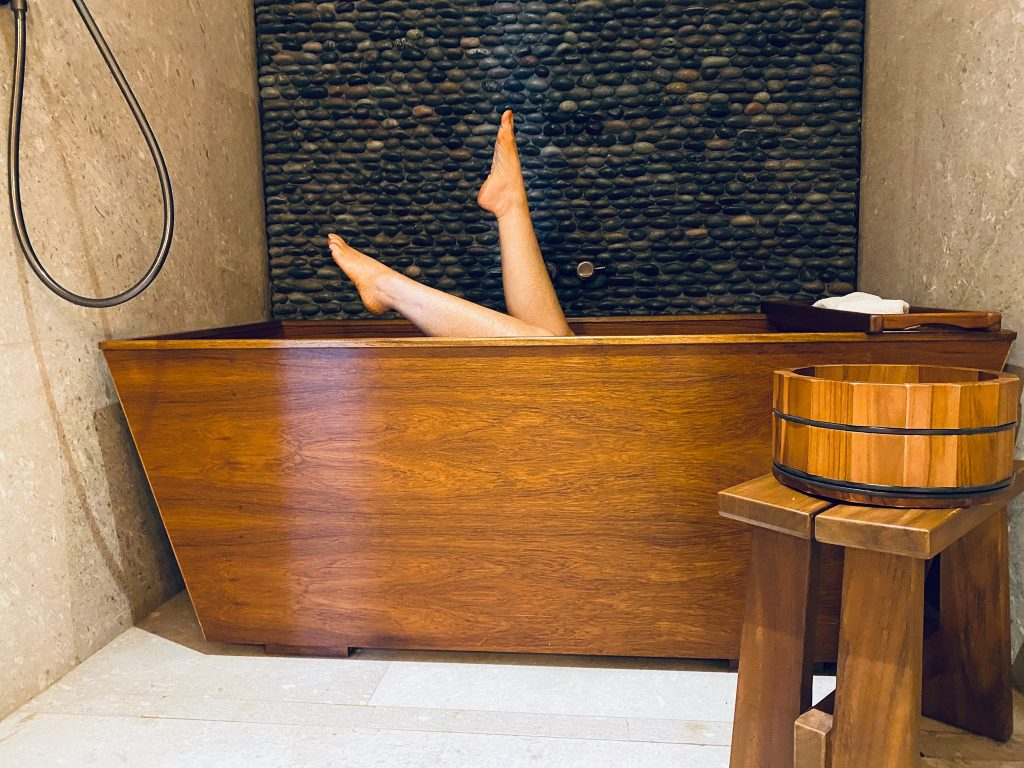 Woman laying in a wooden bathtub with her two feet in the air. | A Guide to Nobu Hotel Los Cabos - A Relaxing Girls Trip