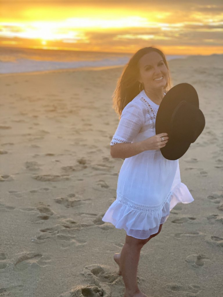 Woman smiling on a beach with the sunset behind her. | A Guide to Nobu Hotel Los Cabos - A Relaxing Girls Trip