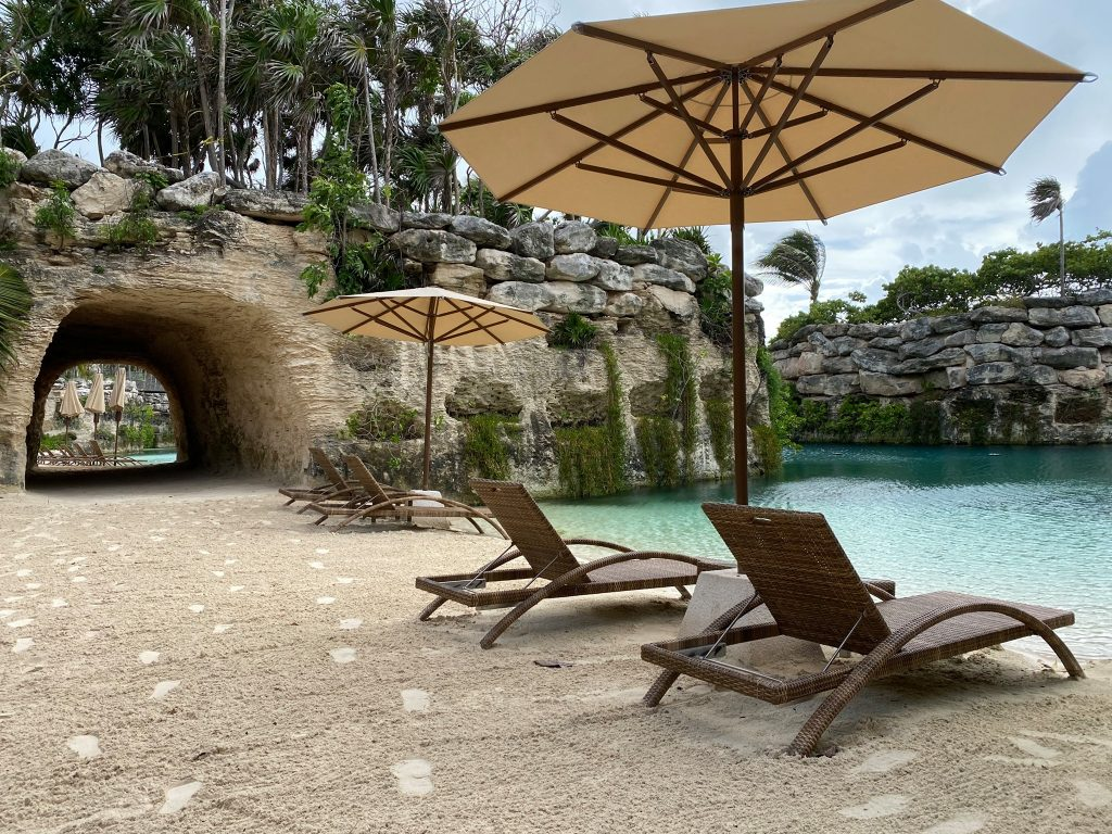 The pool deck filled with lounge chairs.  Guide to Hotel Xcaret in Mexico