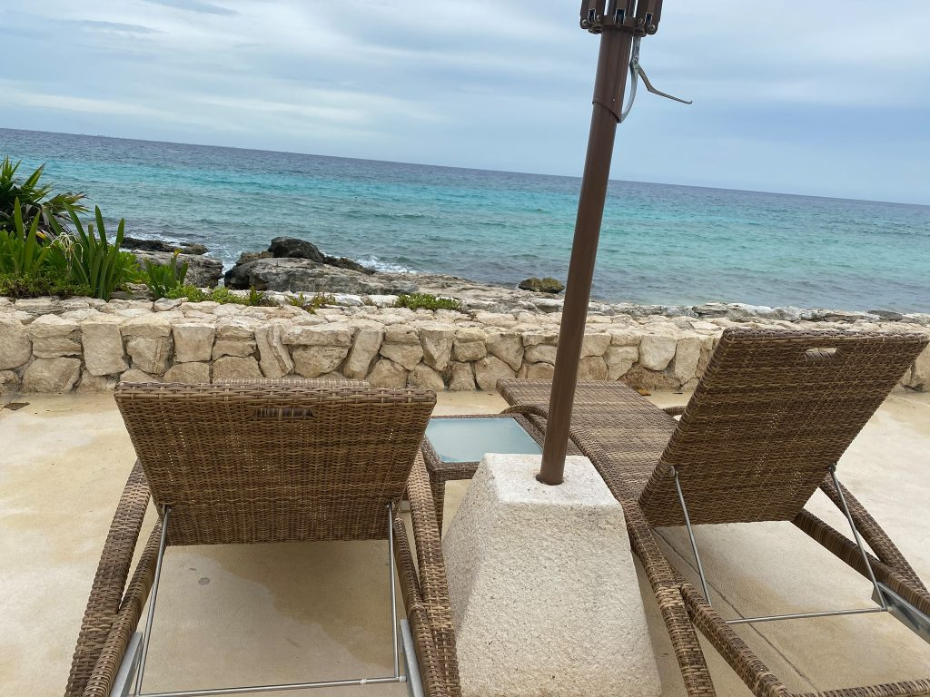 Two lounge chairs at pool facing the ocean.  Guide to Hotel Xcaret in Mexico
