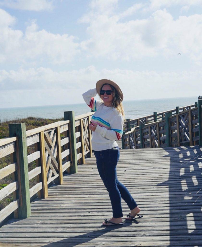 Woman walking on a boardwalk towards the beach. | Lively Beach in Corpus Christi, Texas