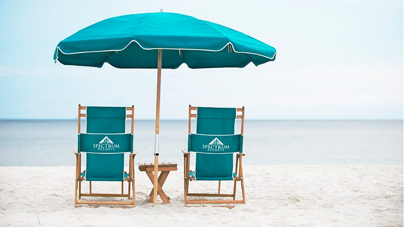 Two beach chairs with an umbrella in the sand on the beach at the shores.   Guide to Gulf Shores & Orange Beach Alabama