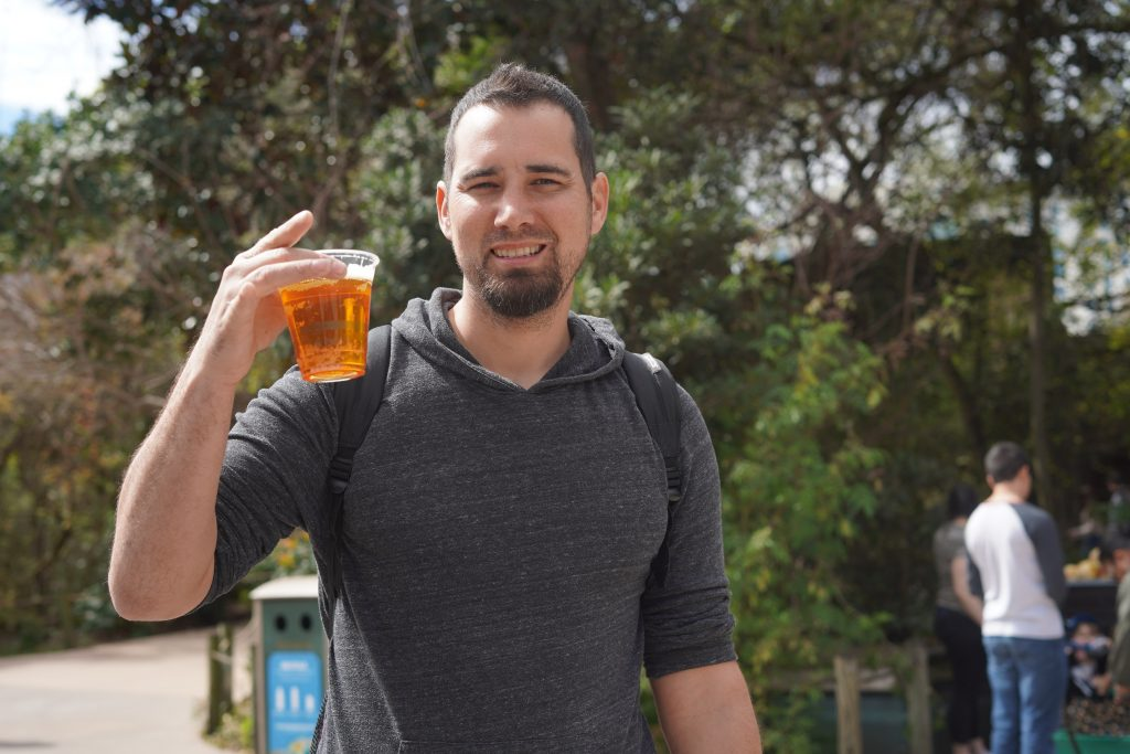 Man holding a beer at the zoo. | The Houston Zoo