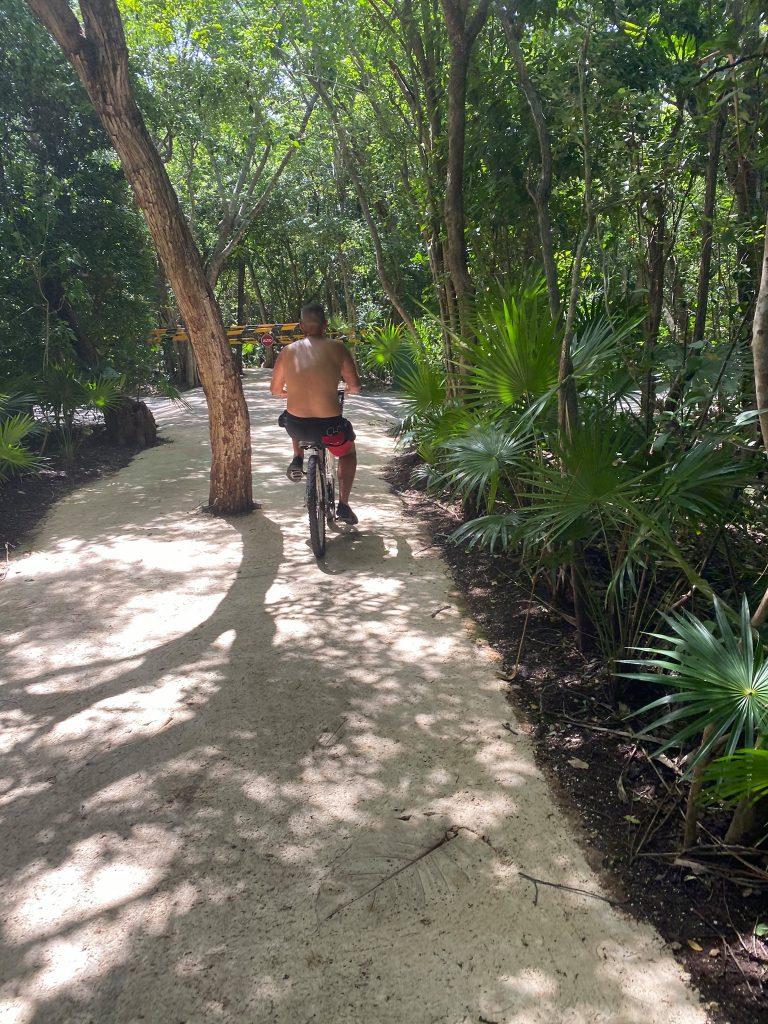 Man riding a bike through the resort. | All About XeI-Ha Park in Riviera Maya