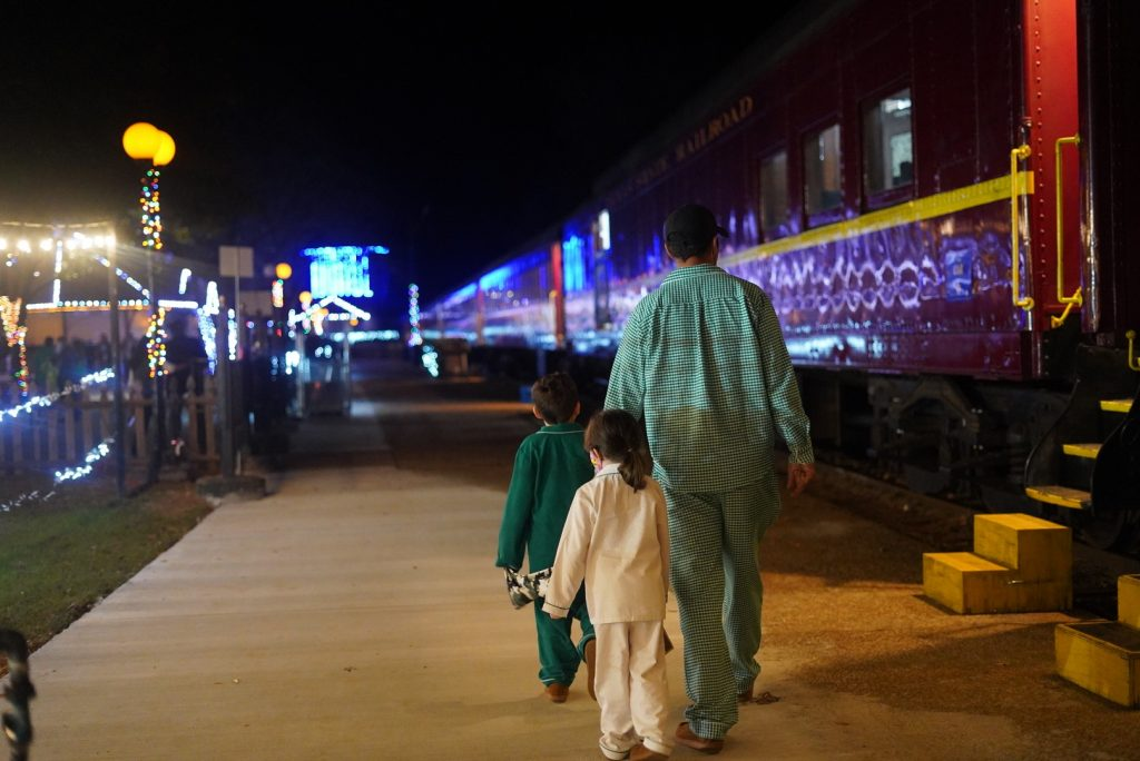 Man with two little kids walking on the sidewalk toward the Polar Express train. | The Polar Express Train Ride in Palestine, Texas