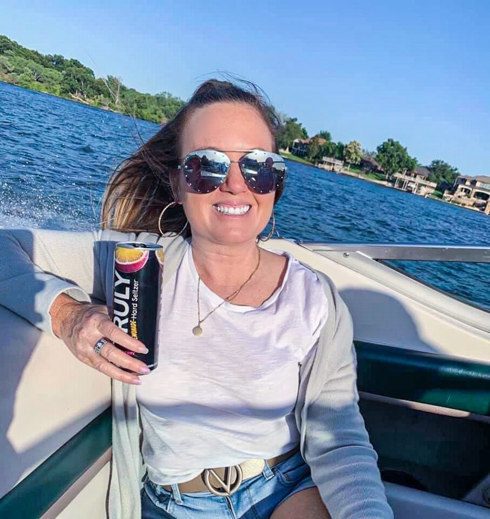 Woman holding a drink on a boat.| Adult Summer Vacation on Lake LBJ