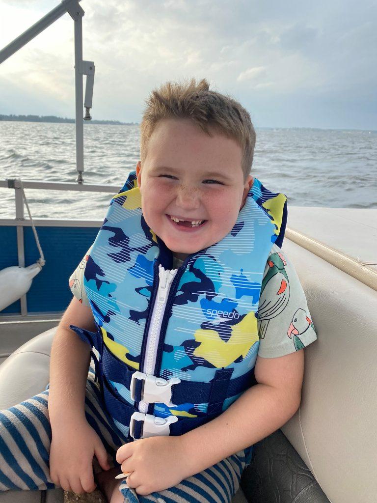 Little boy smiling wearing a lifevest on a pontoon boat on the water. | Margaritaville Lake Resort, Lake Conroe