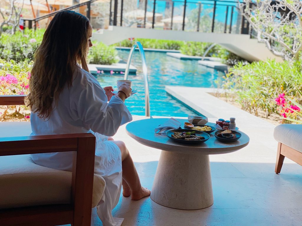 Woman eating breakfast outside her hotel by the pool. | A Guide to Nobu Hotel Los Cabos - A Relaxing Girls Trip
